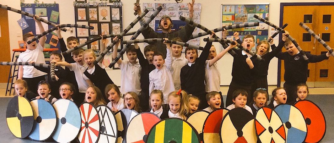 School children wielding Viking shields as part of experience day